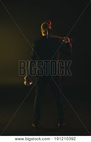 Back View Of Young Man In Tuxedo Holding Ax And Money