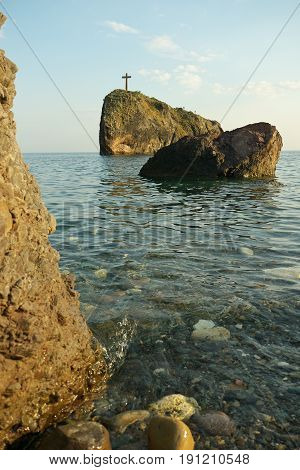 Landscape view of rock with cross and stones on the empty beach the sea at background.