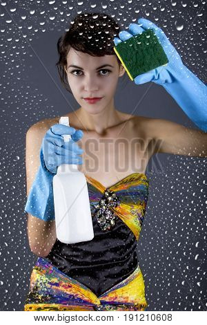 Female model with a spray bottle cleaning transparent glass or lens in a studio. The image depicts a conceptual demonstration of clean photography. She is wiping water with a sponge.