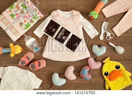 Required accessories of a newborn infant in the expecting period before her born accompanied by her sonography report shot from above in a tabletop flat lay arrangement.
