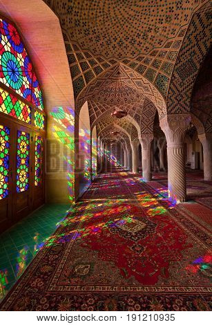 Interior of ornamental Nasir-ol-molk also known as the Pink Mosque in Shiraz with stained glass windows letting colorful ray of light passing through creating beautiful reflections on Persian carpets.