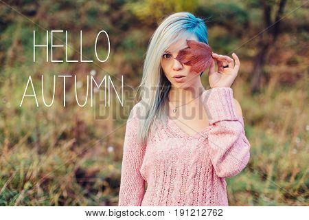 Portrait of a beautiful young woman with red leaf in hands in autumn forest.