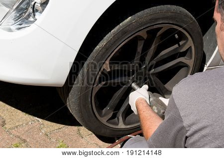 a man changing tyre in street service