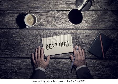 Motivational business concept - Don't Quit with underlined word Do It written on a card lying on a rustic wood desk with a mans hands holding a pen lamp and mug of coffee viewed from above.