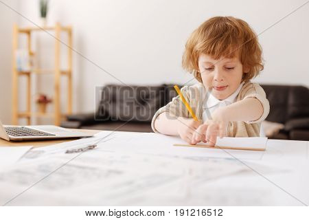 Infatuated with planning. Concentrated boy holding pencil in right hand and using ruler for drawing figure