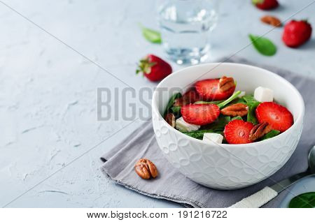 Strawberry spinach goat cheese pecan salad on a grey background