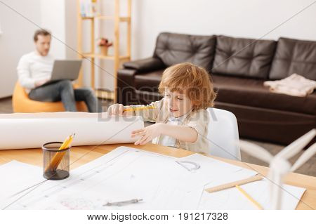 Lets start. Enigmatical blonde man-child keeping smile on his face holding pencil in right hand while looking aside