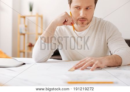 Serious thoughts. Attentive young man sitting at his workplace holding pencil near face while inventing new turbines