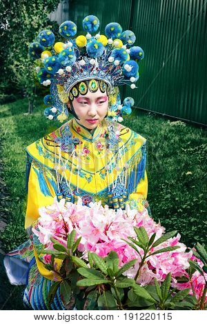 beautiful chinese girl in traditional blue and yellow chinese dress and pompon hat sitting near the pink flower bush