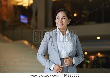 Waist-up portrait of smiling pretty white collar worker looking away thoughtfully while posing for photography in modern office lobby