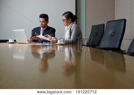 Confident business partners gathered together in modern boardroom and having productive negotiations, waist-up group portrait