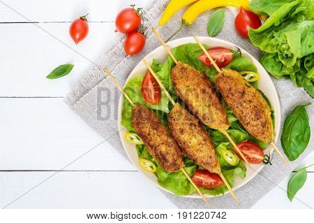 Lula-kebab is a meat dish traditional for the Caucasus in Central Asia and Turkey. Minced meat strung on a skewer and fried. Serve on a plate with lettuce leaves and fresh tomatoes.