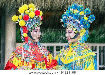 portrait of two beautiful chinese girls in traditional chinese dress and hat with pompons looking each other