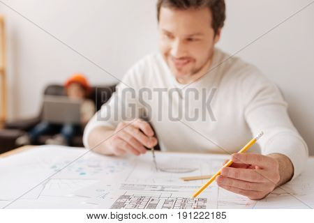 Finally correct. Kind man keeping smile on his face holding stationery while being deep in thoughts