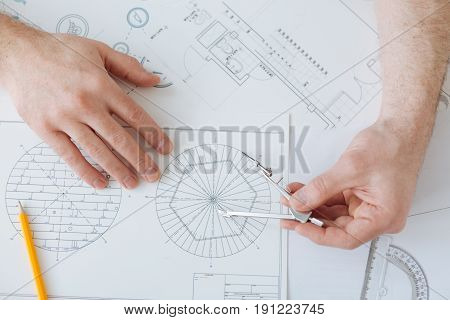 Do it thoroughly. Competent engineer using pair of compasses for making circle and holding hands on the table while working at the moment