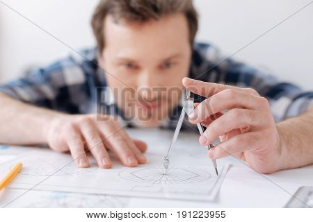 Drawing circle. Attentive man looking forward and holding hands on the paper while inventing new turbine