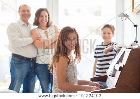 Happy Young Family Listening How Cildren Plays Piano Music