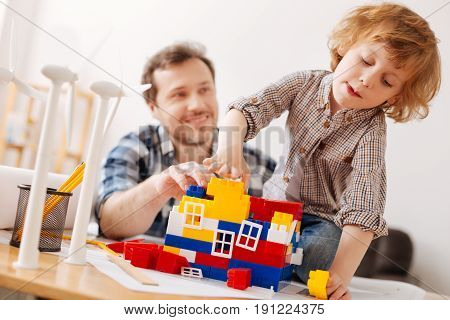 Listen to me. Very attentive boy pressing lips while looking downwards and playing with erector set