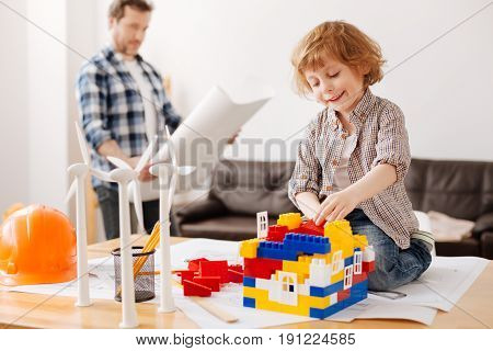 Stylish boy. Delighted child wearing casual clothes and sitting on the table while playing with the erector set
