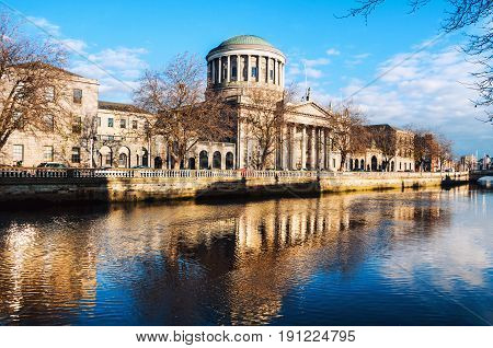 Dublin Ireland. Four courts building in Dublin Ireland with reflection in river Liffey during the sunny evening. cloudy blue sky.