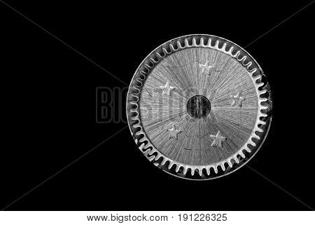 High contrast image of a cogwheel from and old clockwork on a black background.