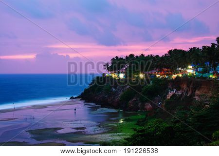 Kerala India. Varkala beach at night various cafes and restaurants at the cliff with colorful sunset sky and motion blurred Laccadive Sea and Papanasam beach in Kerala India
