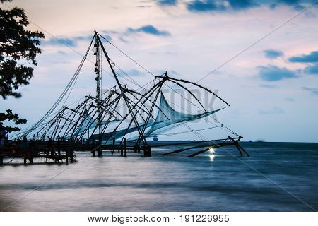 Kerala India. Time-lapse of Chinese fishnets in Cochin Kerala India at sunset. Colorful cloudy sky