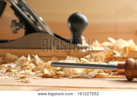 Chisel and saw dust on wooden table in carpenter's workshop, closeup