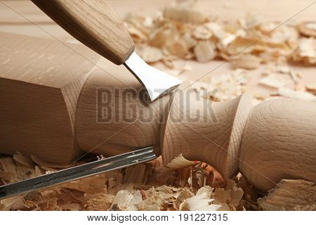 Chiseling wooden part in carpenter's workshop, closeup