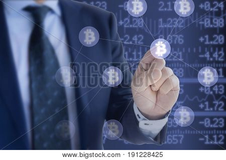 Businessman in blue suit pressing a bitcoin icon in a network