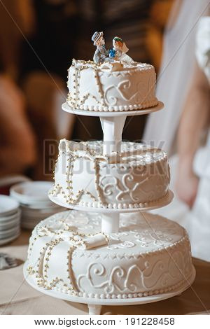 close up of a wedding cake topper in shape of bride and groom