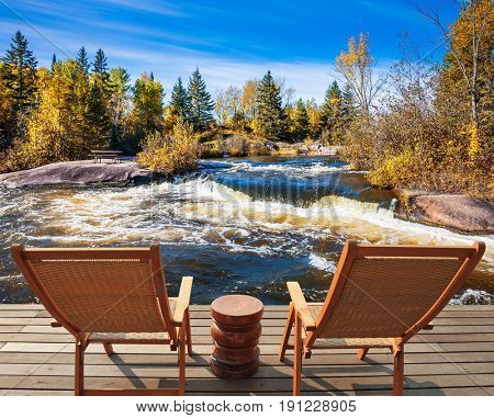 Two deckchairs stand on the shore of Winnipeg River. Foam water rapids on the smooth stones, cirrus clouds and strong wind. Old Pinawa Dam Park, Canada. The concept of recreational tourism