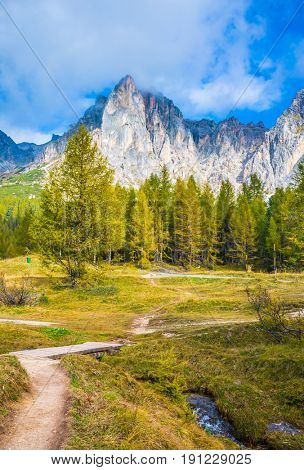 The dizzying Dolomites. Sharp rocks and forest surround the grassy valleys. A cold fast spring flows through the valley. The concept of ecological and extreme tourism