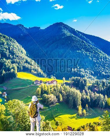 Elderly woman - tourist with backpack travels and takes pictures in Tyrol. Warm autumn in the Val de Funes, Dolomites. The concept of active and ecotourism