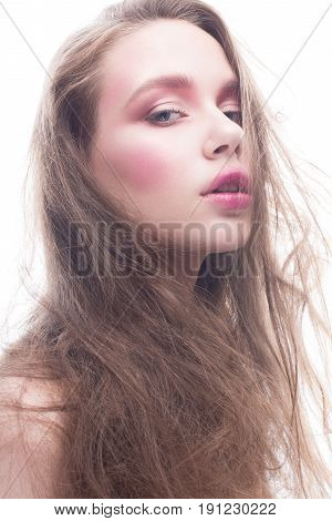 A young girl with loose long hair and bright creative makeup. Beautiful model with red lips and blush on a white isolated background. Pure shining skin. Beauty of the face.