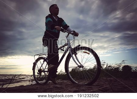 A Man Rides His Mountain Bike On A Beach