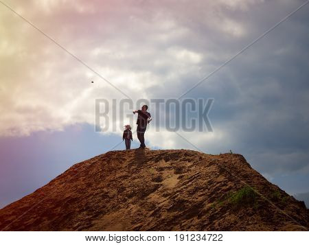 Father and child on the top of the mountain against the sky. Dad throws a stone down from a height