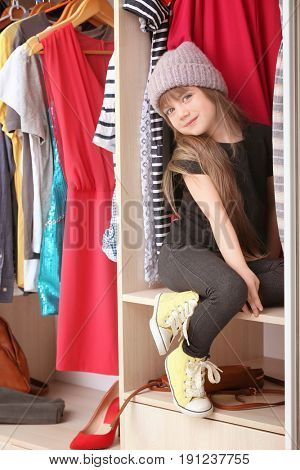 Cute little girl near wardrobe with fashionable clothes at home