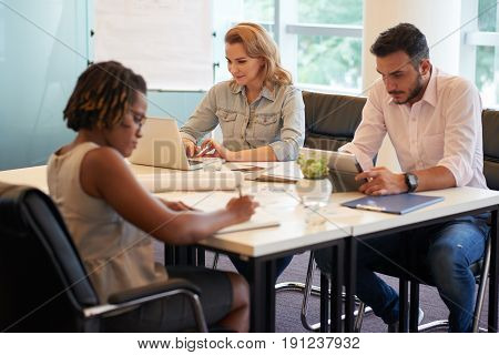 Group of hard-working financial managers preparing annual accounts while sitting in modern boardroom with panoramic windows