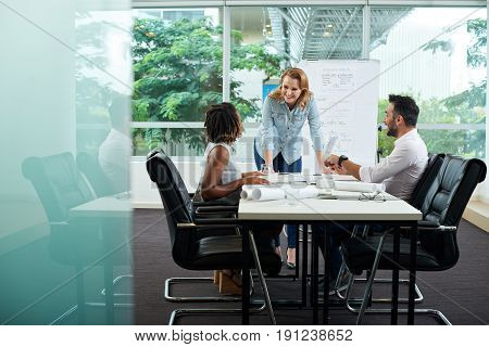 Cheerful multi-ethnic group of creative designers gathered together in cozy boardroom with panoramic windows and working on promising project