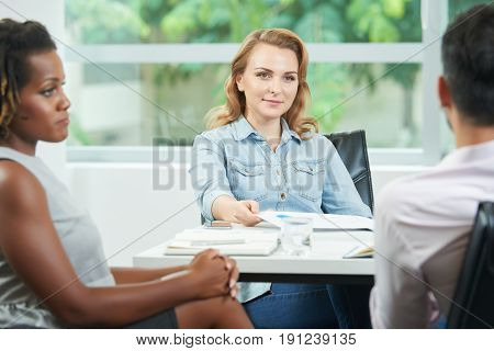 Waist-up portrait of attractive young entrepreneur listening to her male business partner with interest while conducting negotiations in modern boardroom