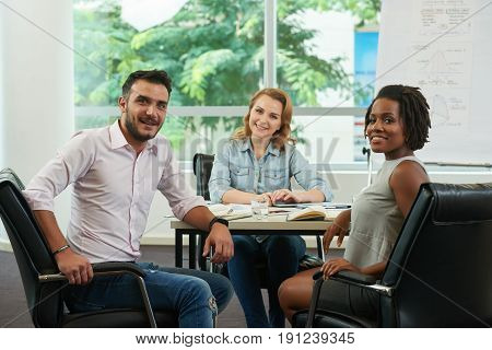 Multi-ethnic group of joyful colleagues posing for photography while having working meeting in spacious boardroom with panoramic windows