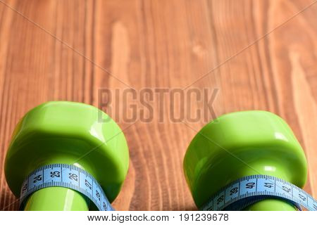 Pair Of Green Dumbbells In Closeup And Blue Measuring Tape