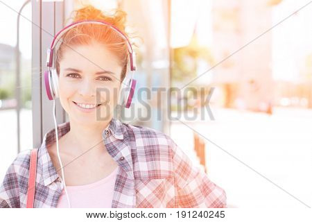 Portrait of happy woman wearing headphones while waiting at bus stop