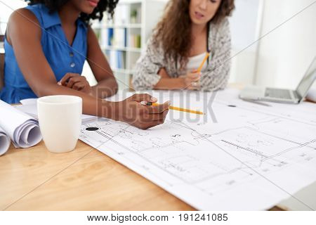 Multi-ethic group of engineers gathered together in open plan office and working on blueprint, wooden desk on foreground