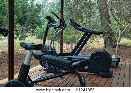 Gym with fitness equipment in forest workout, active