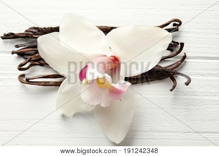 Dried vanilla sticks and flower on light wooden background, closeup