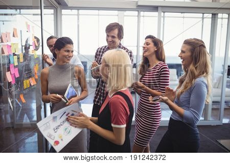 Cheerful business people making plans with adhesive notes in creative office