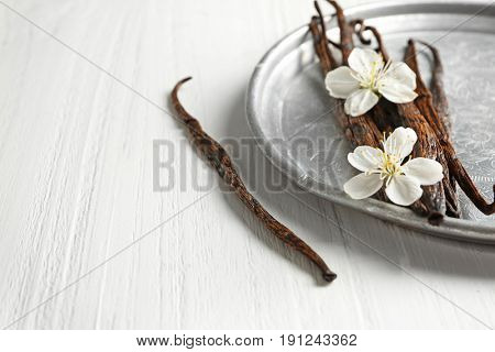 Composition with dried vanilla sticks on light wooden table, closeup