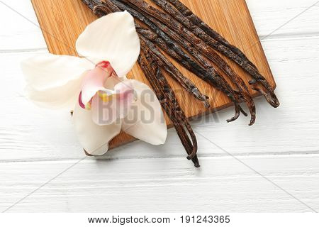 Dried vanilla sticks, flower and board on light wooden background, closeup